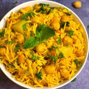 Chole Biryani served in a bowl with cooked chickpeas on side