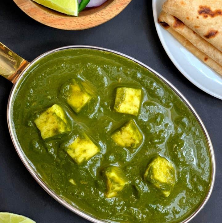 instant pot palak paneer served in a copper bottom serving dish with chapati and lemon on side