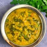 Moringa/drumstick leaves moong dal in a steel bowl with drumstick leaves on side