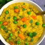 vegetable quinoa khichdi in a white bowl prepared in instant pot and coriander on side