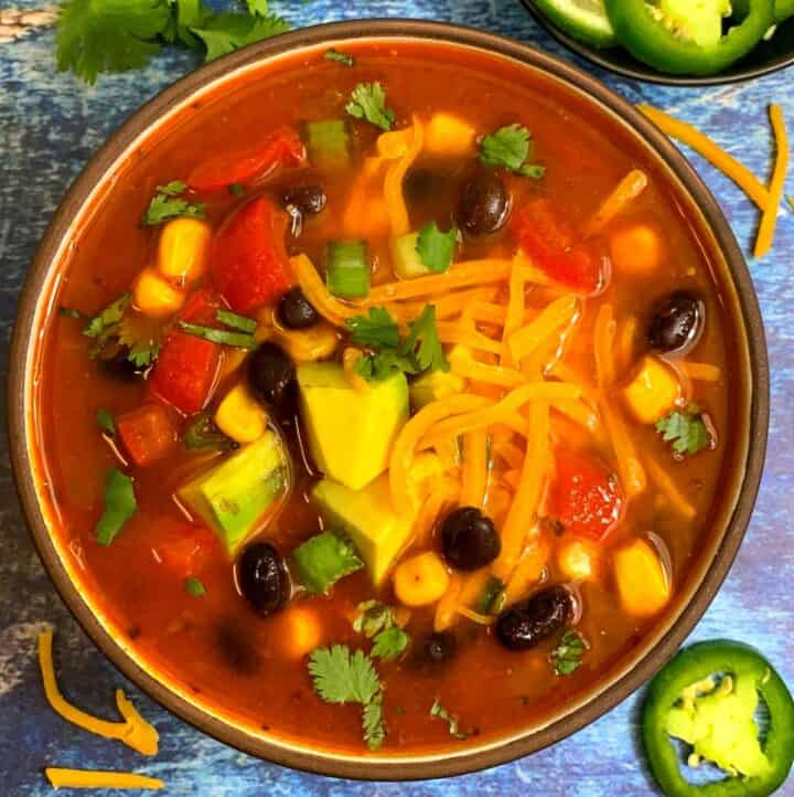 Vegetarian Taco Soup served in a bowl topped with cheese beans and avocado