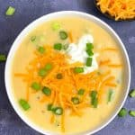 instant pot cheesy potato soup served in a white bowl topped with cheddar cheese and green onions and with side of cheddar cheese