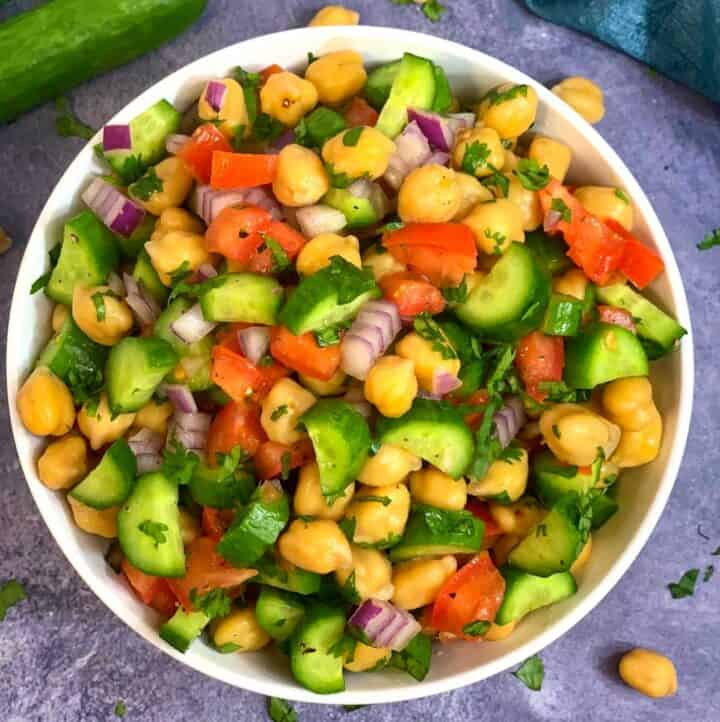 Chickpea Cucumber Tomato Salad served in a bowl with whole cucumber on side