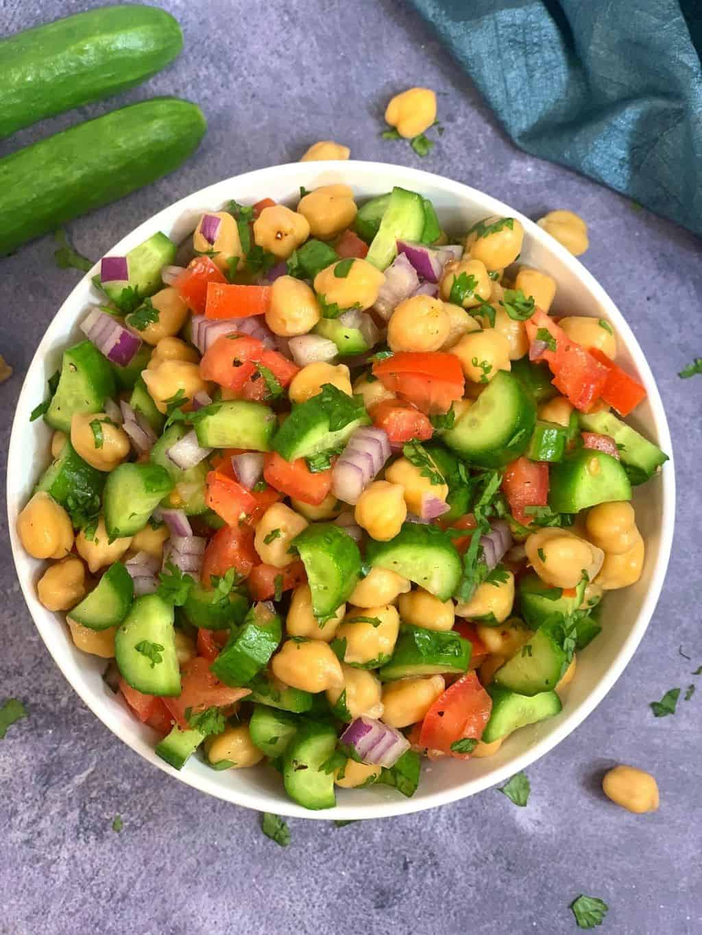 chickpea cucumber tomato salad recipe  served in a white bowl with whole cucumber on side