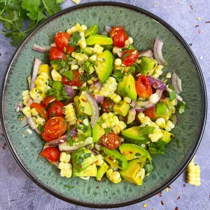 avocado corn tomato salad served in a bowl with cilantro and cut avocado on the side