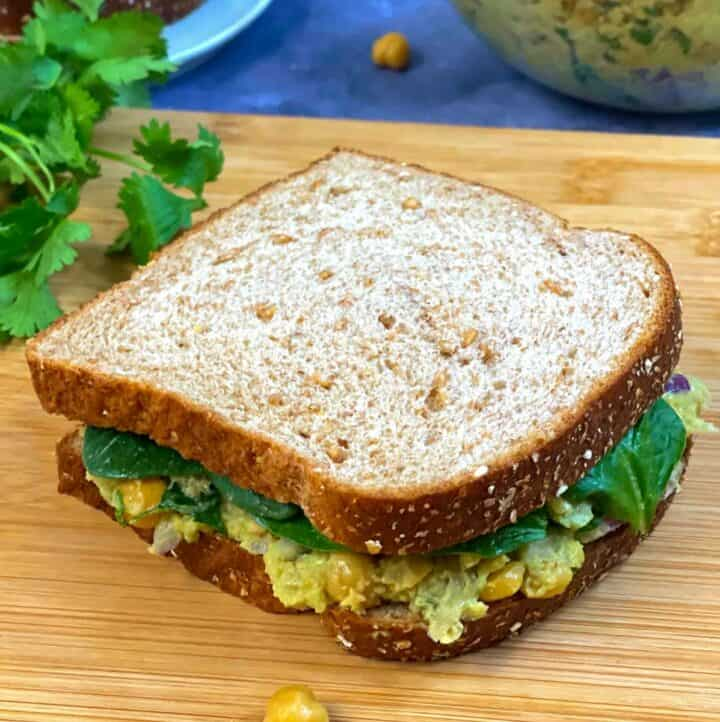 chickpea avocado salad sandwich served on wooden plank with side of cilantro