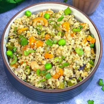 quinoa upma served in a bowl with masala chai on the side